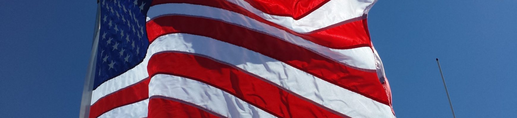 American Flag waving in the wind, with blue sky behind it.