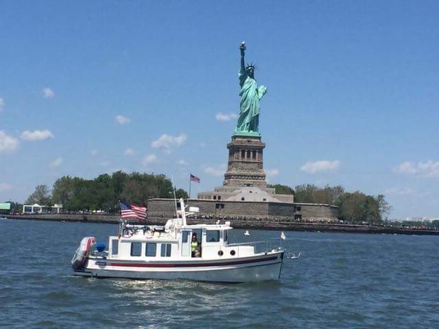 Statue of Liberty with boat crossing in front of it.