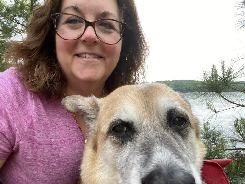 The author is wearing a pink shirt, and smiling into the camera with her dog, Lucy in the foreground. There is a lake in the background.